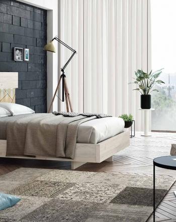 Habitación de cama grande de acabados claros y luminosos.