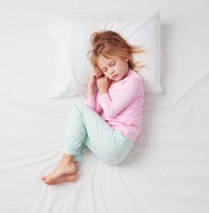 Top view of little girl sleeping in Foetus pose