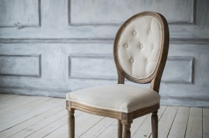 White vintage chair standing in front of a light wall